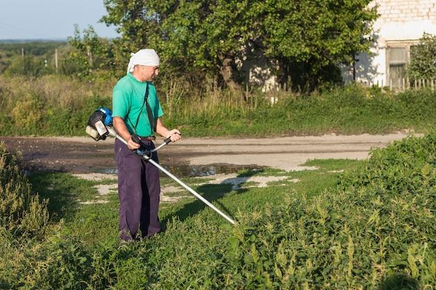 Hombre en la granja cosiendo hierba con cortacésped