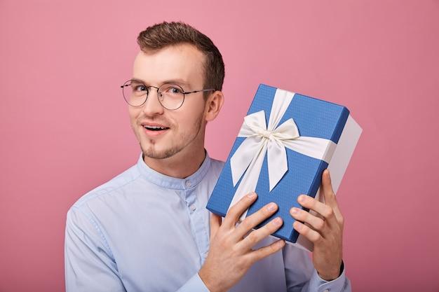 Hombre gratamente sorprendido en camisa delicadamente azul con gafas mira el marco con sorpresa