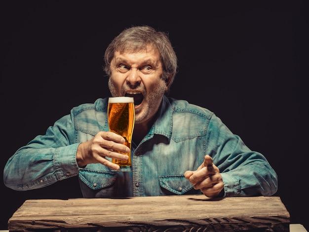 El hombre gritando en camisa vaquera con vaso de cerveza