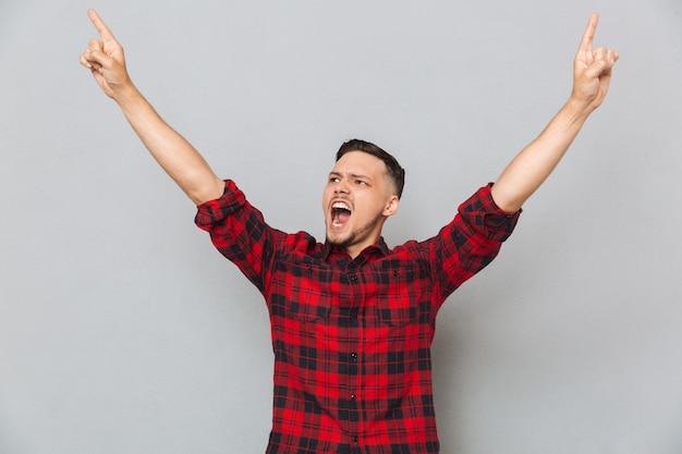 Hombre gritando feliz apuntando hacia arriba