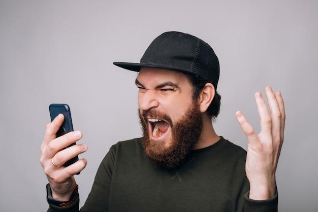 Hombre gritando está mirando a su teléfono sobre fondo blanco.