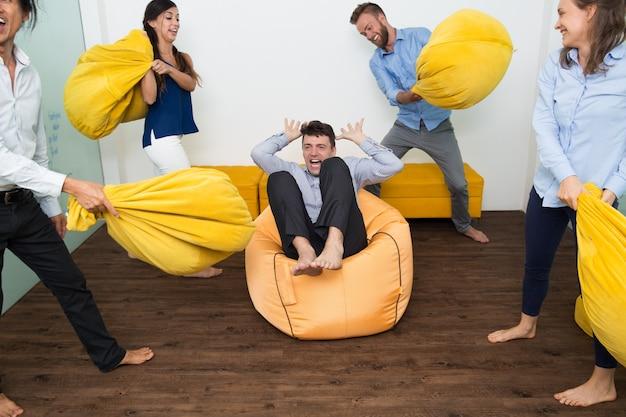 Hombre gritando que es golpeado con almohadas de amigos