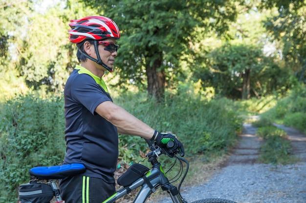 Hombre con guante de casco para seguridad montando una bicicleta en un camino rural a lo largo de un bosque