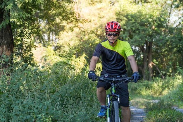 Hombre con guante de casco para la seguridad que monta una bicicleta en el camino rural a lo largo de un bosque