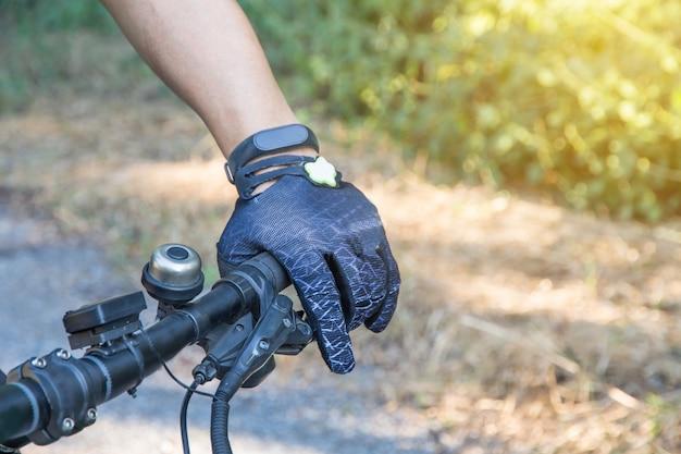Hombre con guante de casco para la seguridad que monta una bicicleta en la carretera del campo a lo largo de un bosque, montar a campo traviesa