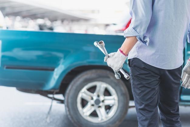 Un hombre con guantes blancos y sosteniendo una llave cruzada