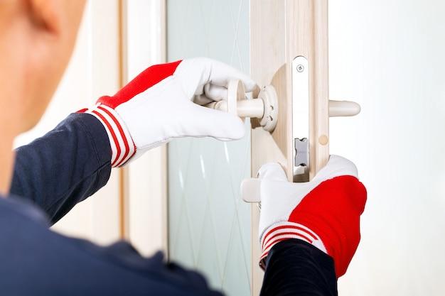 Hombre en guantes cambia las cerraduras de las puertas. manitas reparar la cerradura de la puerta de la habitación.