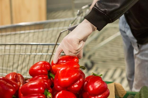 Hombre en guantes de látex blanco elegir pimiento rojo en la tienda. precauciones durante la cuarentena