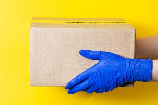 Un hombre con guantes de látex entrega un paquete. el concepto de entrega segura de bienes durante la pandemia de coronavirus.