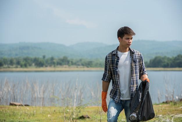 Un hombre con guantes naranjas recogiendo basura en una bolsa negra.