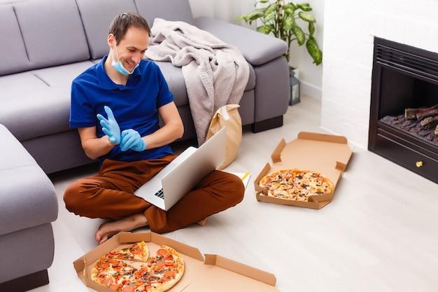 Hombre con guantes protectores y máscara con laptop para pedidos de alimentos en línea durante la cuarentena, primer plano. servicio de entrega