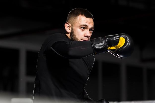Hombre en guantes protectores posando mientras boxeo