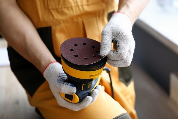Hombre en guantes de trabajo tiene máquina lijadora de herramientas