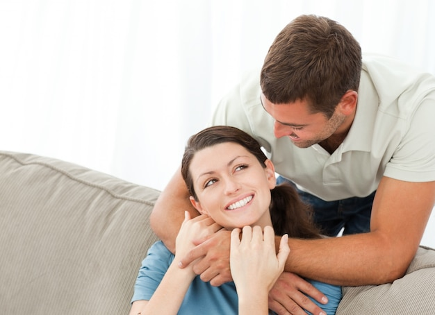 Hombre guapo abrazando a su esposa mientras descansa en el sofá