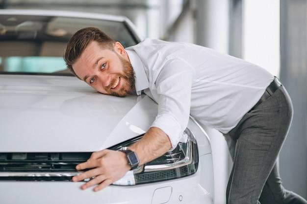 Hombre guapo abrazando un coche en una sala de exposición