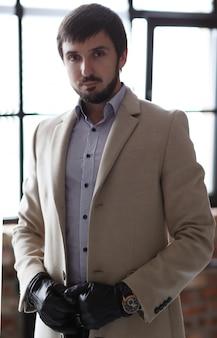 Hombre guapo con abrigo beige