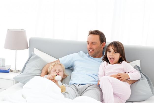 Hombre guapo con acostado en su cama con sus hijos en waiking