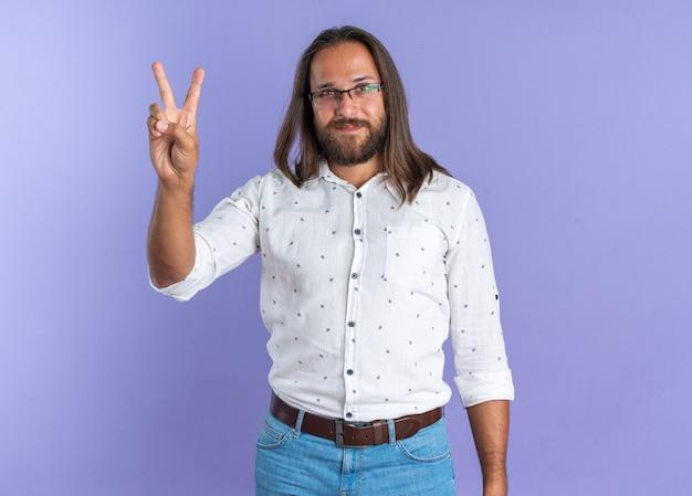 Hombre guapo adulto complacido con gafas haciendo el signo de la paz