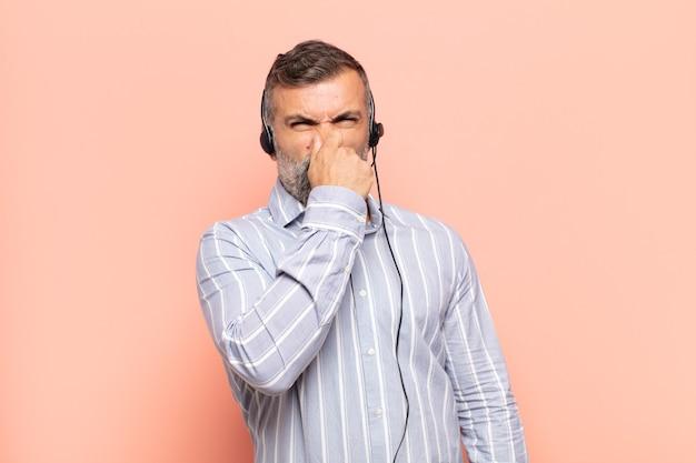 Hombre guapo adulto que se siente disgustado, tapándose la nariz para evitar oler un hedor desagradable y desagradable