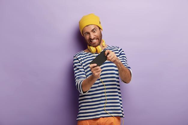 El hombre guapo sin afeitar sostiene el teléfono inteligente en posición horizontal, disfruta de una nueva aplicación increíble, juega en línea, se divierte en el interior, usa un sombrero amarillo y el saltador de marinero lucha por ganar la competencia obtiene la puntuación más alta