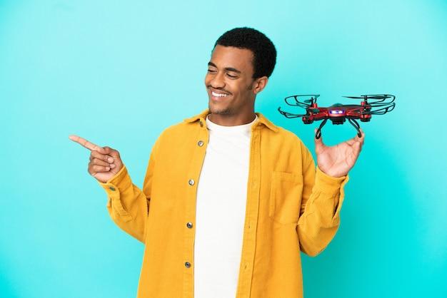 Hombre guapo afroamericano sosteniendo un avión no tripulado sobre fondo azul aislado apuntando con el dedo hacia el lado y presentando un producto
