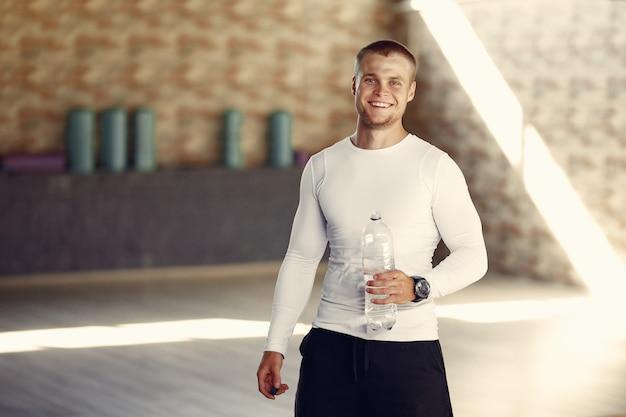 Hombre guapo agua potable en el gimnasio