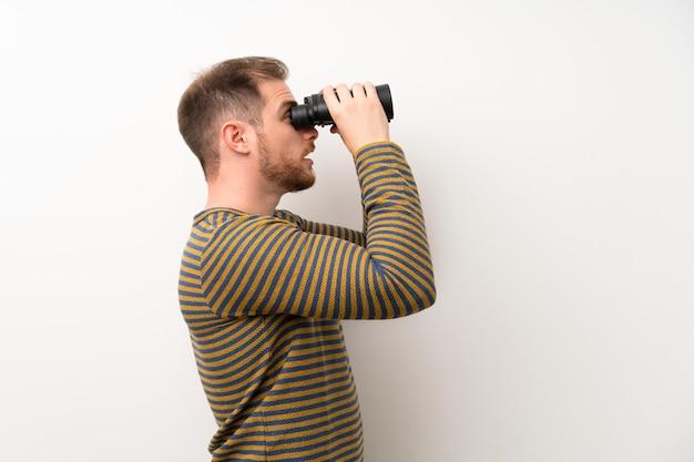 Hombre guapo aislado pared blanca con binoculares negros