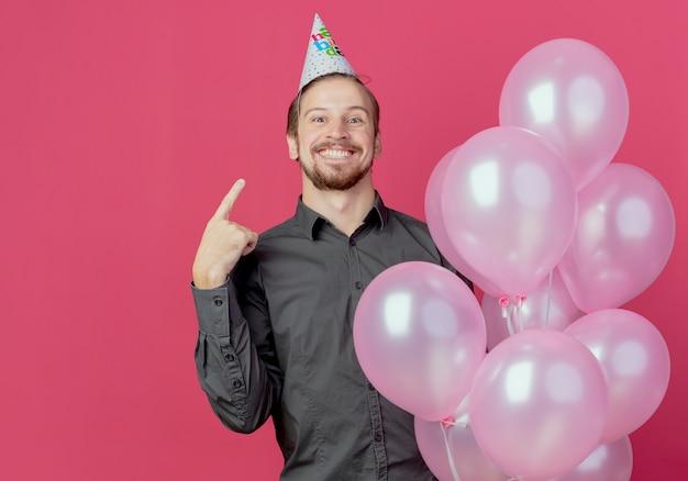 Hombre guapo alegre en gorra de cumpleaños se encuentra con globos de helio apuntando a la tapa aislada en la pared rosa