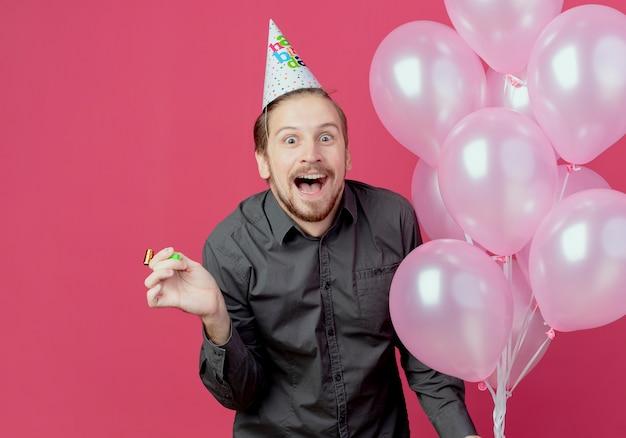Hombre guapo alegre en gorro de cumpleaños se encuentra con globos de helio con silbato aislado en la pared rosa
