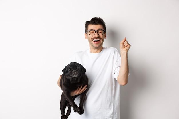 Hombre guapo alegre con perro regocijándose, celebrando la victoria. chico feliz lleva lindo pug negro y mirando optimista, adoptando mascota, de pie sobre fondo blanco.