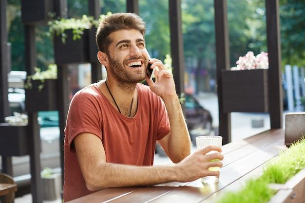 Hombre guapo alegre riendo y sonriendo mientras habla por teléfono móvil desde la cafetería al aire libre