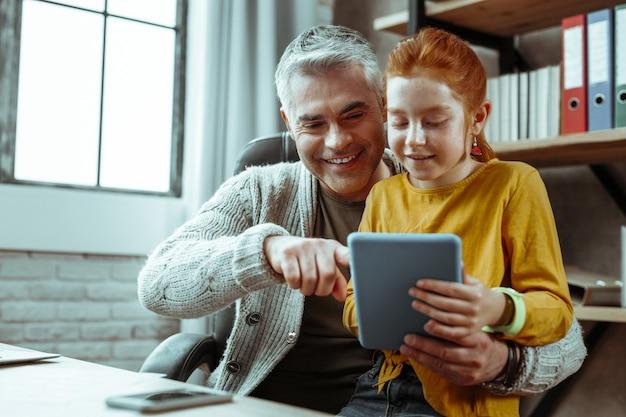Hombre guapo alegre sonriendo mientras muestra la tableta a su hija
