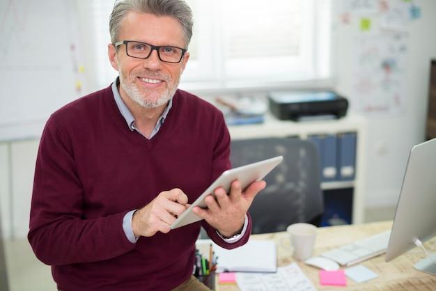Hombre guapo y alegre trabajando en tableta digital
