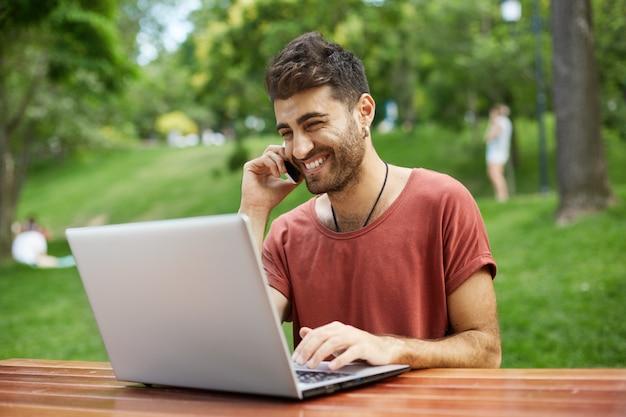 Hombre guapo alegre usando laptop en el parque y hablando por teléfono feliz