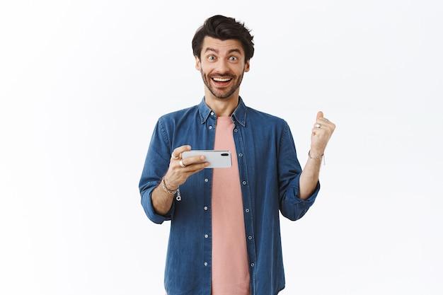 Hombre guapo aliviado feliz, sosteniendo el teléfono inteligente horizontalmente y la bomba de puño sintiéndose afortunado, ganando el premio en el juego, se ve asombrado, sonriendo con alegría, celebrando la victoria, pared blanca