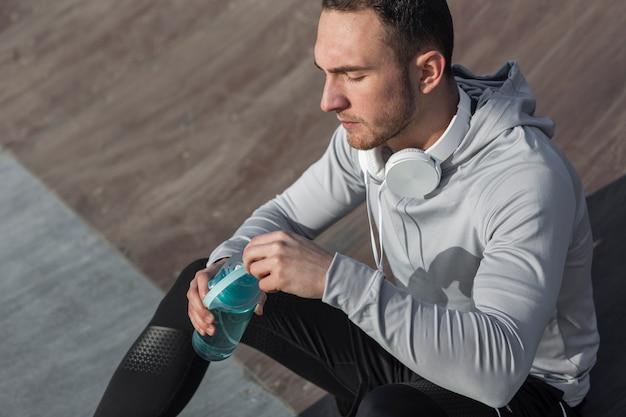 Hombre guapo de alto ángulo sosteniendo una botella de agua
