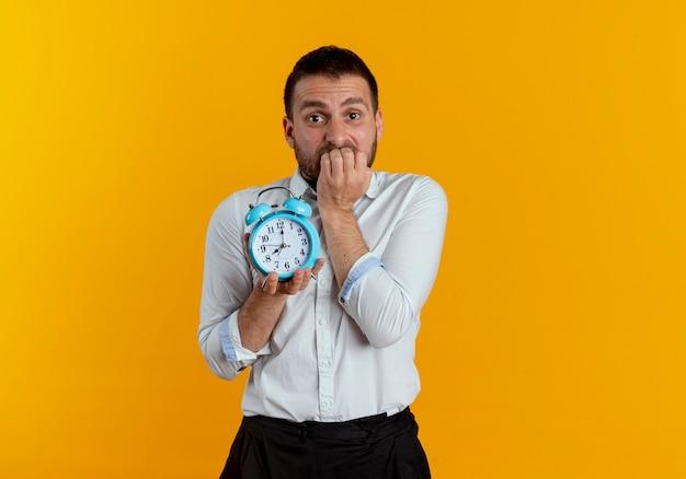 Hombre guapo ansioso muerde los dedos sosteniendo el despertador aislado en la pared naranja