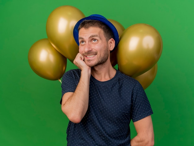 Hombre guapo ansioso vestido con gorro de fiesta azul pone la mano en la barbilla mirando hacia arriba sostiene globos de helio aislados en la pared verde