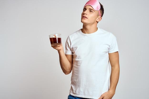 Hombre guapo con antifaz rosa para dormir con una taza de té