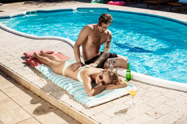 Hombre guapo, aplicar la crema bronceadora en mujer cerca de la piscina