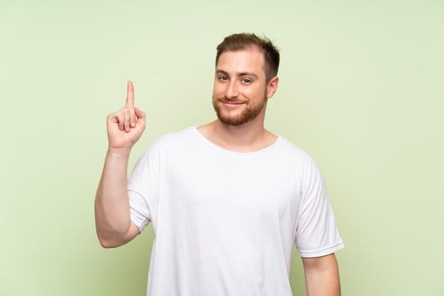 Hombre guapo apuntando con el dedo índice una gran idea.