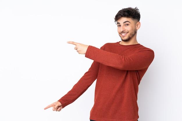 Hombre guapo árabe sobre pared aislada apuntando con el dedo hacia un lado y presentando un producto