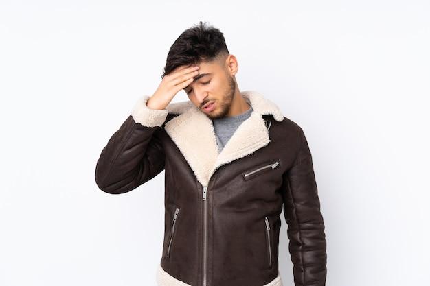Hombre guapo árabe sobre pared aislada con dolor de cabeza