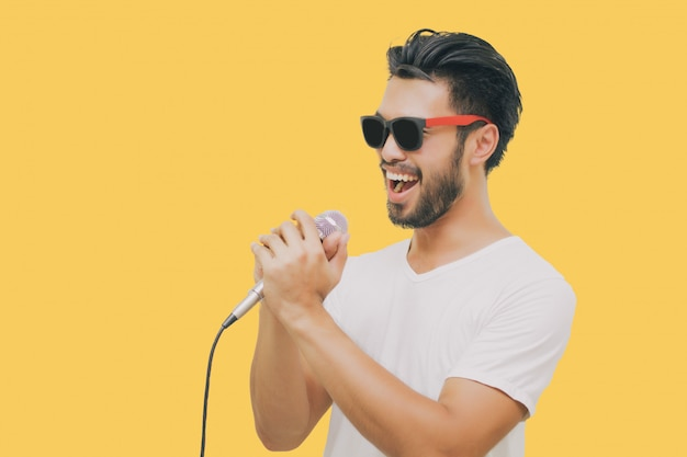 Hombre guapo asiático con bigote, sonriendo y cantando al micrófono aislado sobre fondo amarillo