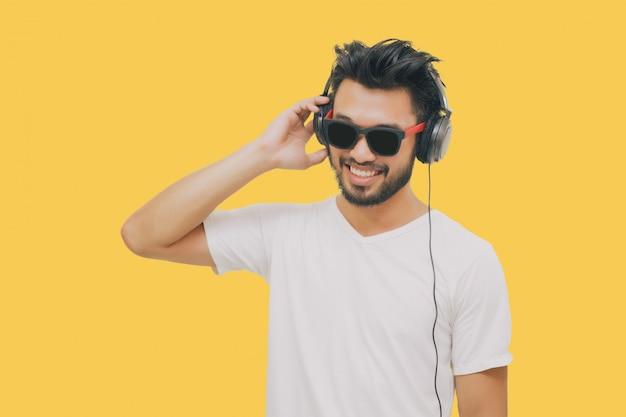 Hombre guapo asiático con bigote, sonriendo y riendo y usando un teléfono inteligente para escuchar música con auriculares sobre fondo amarillo