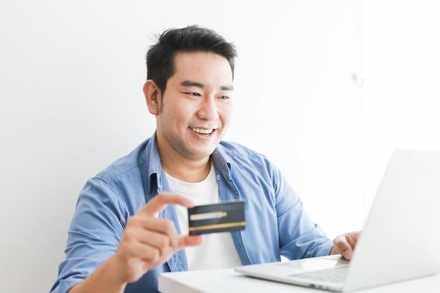 Hombre guapo asiático en camisa azul con tarjeta de crédito con computadora portátil de compras en línea