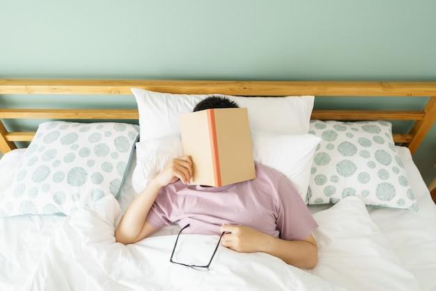 Hombre guapo asiático leer libros mientras duerme.