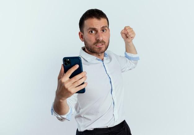 Hombre guapo asustado sostiene el teléfono y levanta el puño listo para perforar aislado en la pared blanca