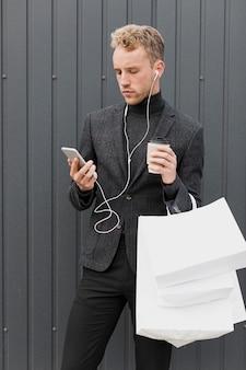 Hombre guapo con auriculares cerca de una pared gris