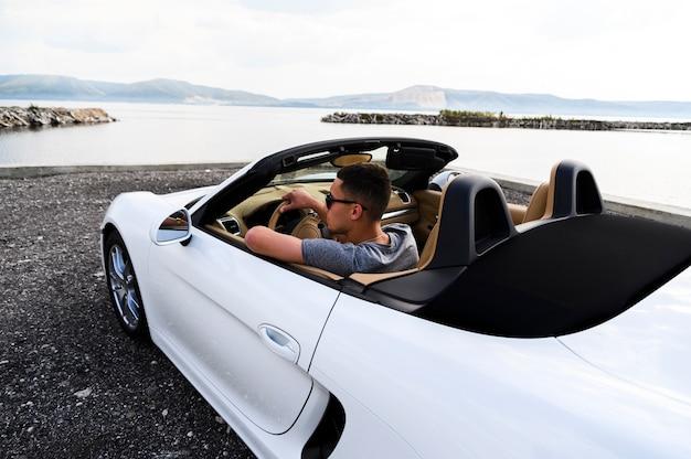 Hombre guapo en auto blanco